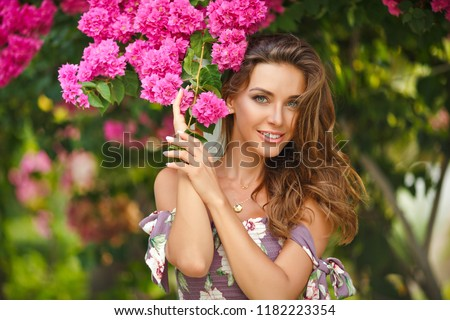 Portrait of a very beautiful sensual and sexy girl in a long dress, summer in the garden on a background of flowers