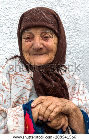 Portrait of a very lonely old woman with merry eyes and happy, happy face, with deep wrinkles multiple