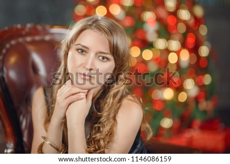 Portrait of a very pretty brunette girl at Christmas in the interiors. Close-up portrait of beautiful sexy young woman with long brown hair over brown background #1146086159
