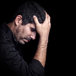 Portrait of a very sad young hispanic man with a thoughtful expression on a black background with space for text