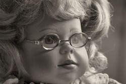 Portrait of a vintage baby doll, toy girl with blond hair and glasses.