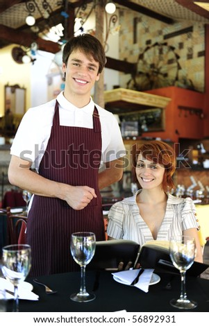portrait of a waiter and happy costumer at the restaurant - stock photo