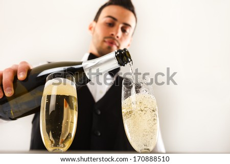 Portrait of a waiter pouring champagne into a flute