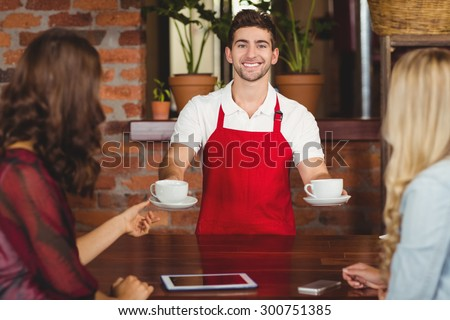 Portrait of a waiter serving coffees to customers at the coffee shop