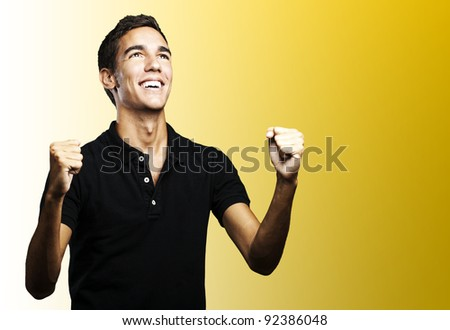 portrait of a winner young man looking up over yellow background