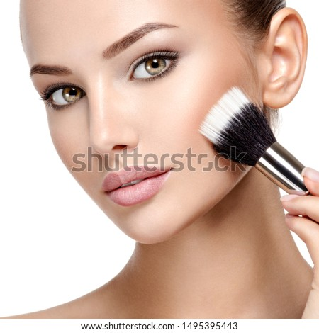 Portrait of a woman  applying cosmetic makeup on the face using makeup brush.  #1495395443