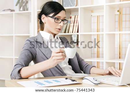 Portrait of a woman at the office for a portable computer with a cup of coffee