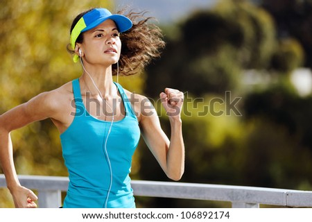 Portrait of a woman athlete runner training outdoors with cap and headphones listening to music. endurance sport.