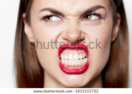 Portrait of a woman bares her teeth and looks aside a grimace  Сток-фото ©