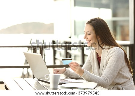 Portrait of a woman buying on line or booking hotel with a laptop and credit card on the beach in vacations. E commerce concept