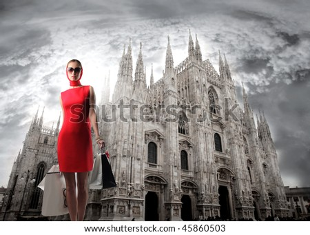 Portrait of a woman carrying some shopping bags in front of the Dome of Milan