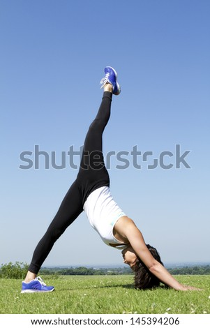 Portrait of a Woman comfortably doing a Yoga Stretch outdoors