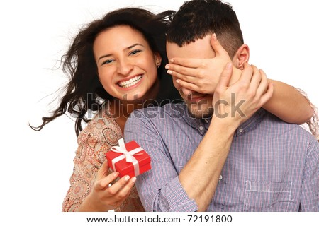 Portrait of a woman covering her husband's eyes to surprise him with a gift