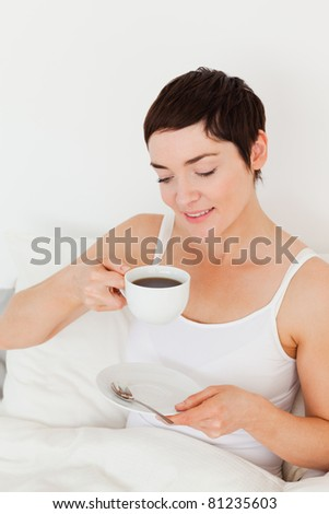 Portrait of a woman drinking coffee in her bedroom