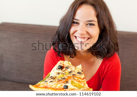 Portrait of a woman eating a pizza with a big smile