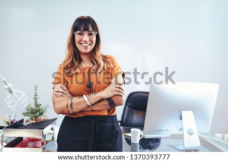 Portrait of a woman entrepreneur standing in office with arms crossed. Smiling businesswoman in eyeglasses standing near her desk in office.