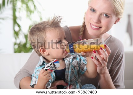 portrait of a woman feeding her son - stock photo