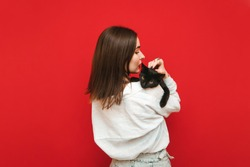 Portrait of a woman from the back holding a cat on her shoulders hugging and stroking, the cat looks into the camera. Back of beautiful girl with black cat on shoulders on red background.