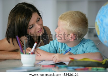 Portrait of a woman helping a boy to do homework