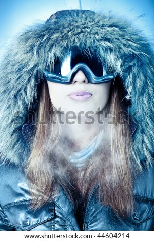 Portrait of a woman in a hood and goggles executed in cold tones.