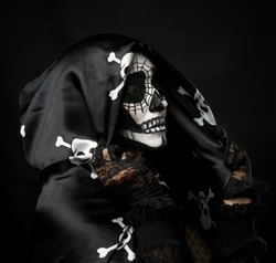 portrait of a woman in a make-up of a skeleton dressed in a black cloak with a cap, festive image for Halloween