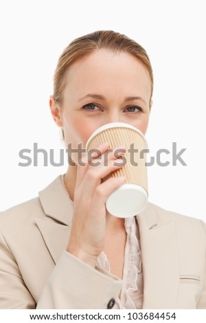 Portrait of a woman in a suit drinking a takeaway coffee against white background