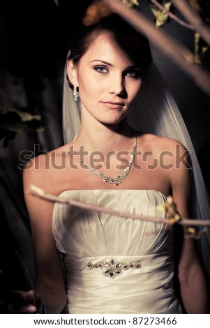 Portrait of a woman in a wedding dress among the branches