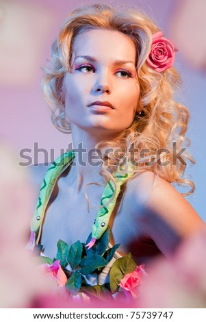 stock photo : Portrait of a woman in flowers depicting bible woman Eva with snake on her neck