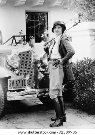 Portrait of a woman in front of her car in a riding outfit