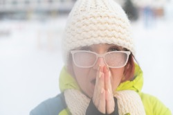 Portrait of a woman in glasses covered with hoarfrost. The girl is freezing and forgot gloves in very cold weather and blows on her bare hands
