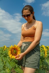 Portrait of a Woman in Glasses Standing in a Field of Sunflowers on a Sunny Warm Summer Day. The concept of Beauty and Unity with Nature. Woman and Sunflower. Farmer Female Hand Holds Sunflower Flower