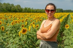 Portrait of a Woman in Glasses Standing in a Field of Sunflowers on a Sunny Warm Summer Day. The concept of Beauty and Unity with Nature. Woman and Sunflower.