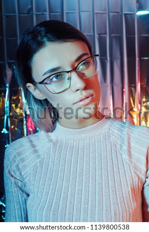 Portrait of a woman in neon colored reflection glasses in the background. Good vision, perfect makeup on girl face. Art portrait of a flare and bokeh on the glasses. Vision restoration, eye surgery