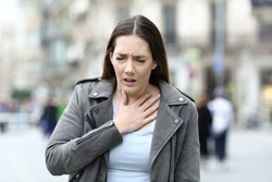 Portrait of a woman in pain holding her chest suffering from lack of breath on a city street