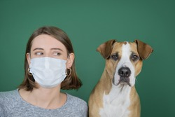 Portrait of a woman in protective mask looking at her dog. Coronavirus, COVID-19 pandemic concept. Domestic animal allergy concept, sneezing and coughing in presence of pets