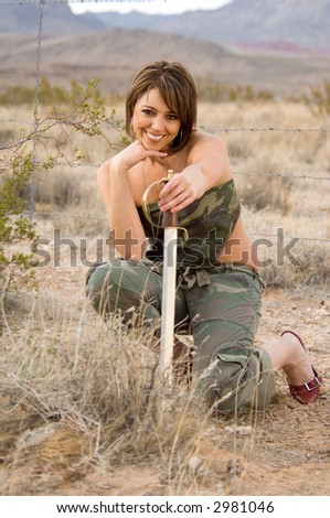 Portrait of a woman in the desert crouched behind a bush in the desert holding a sword