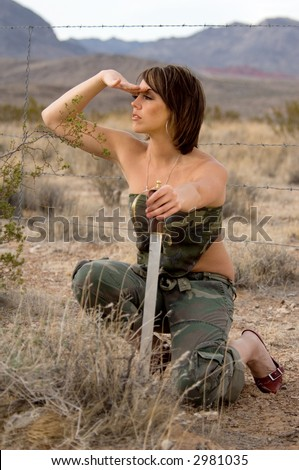 Portrait of a woman in the desert crouched behind a bush in the desert holding a sword and scanning the horizon