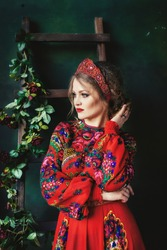 Portrait of a woman in the Russian style. A beautiful Russian girl in a kokoshnik (crown) and in a traditional dress looks sideways. Russian folk, retro, ethno. Pavlovo Posad shawl. Selective focus