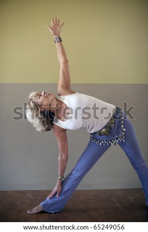 Portrait of a woman in the yoga pose triangle indoors.