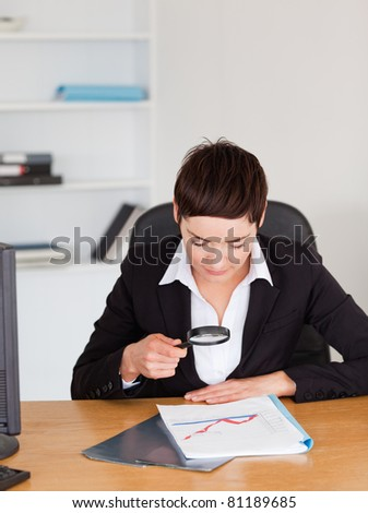 Portrait of a woman looking at a chart with a magnifying glass in her office