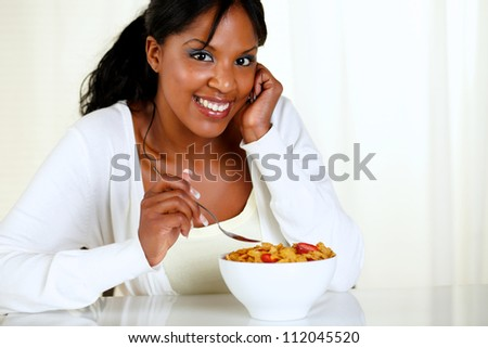 Portrait of a woman looking at you and eating a bowl of cereals with strawberries at soft colors composition. with copyspace
