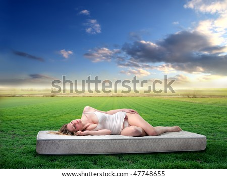 Portrait of a woman lying on a mattress on a green field