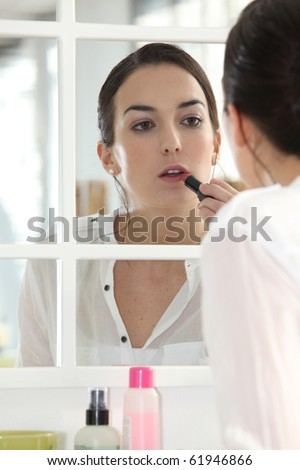 Portrait of a woman making up her lips
