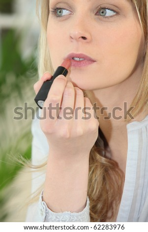 Portrait of a woman making up lips