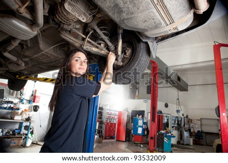 Portrait of a woman mechanic working on the underside of a car