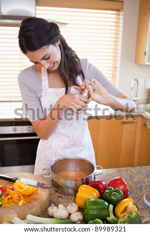 Portrait of a woman preparing a sauce in her kitchen