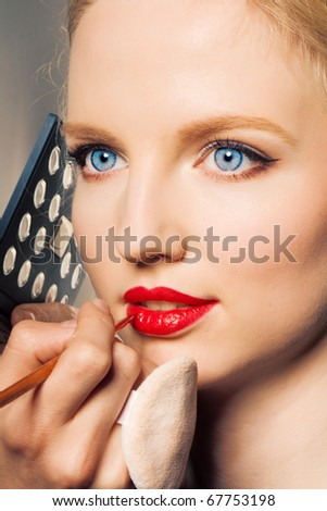 Portrait of a woman putting on lip liner.