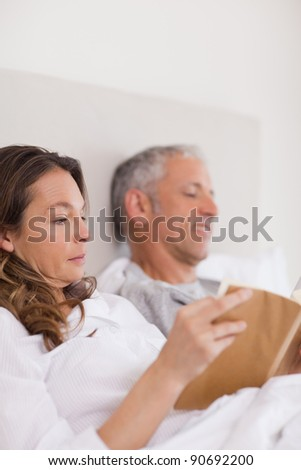 Portrait of a woman reading a book while her husband is reading a newspaper in their bedroom