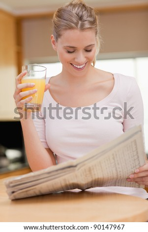 Portrait of a woman reading the news while drinking orange juice in her kitchen