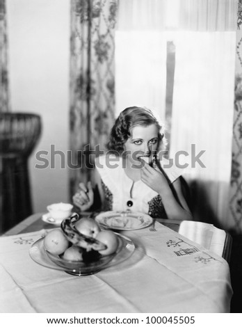 Portrait of a woman sitting at a table and eating a piece of bread